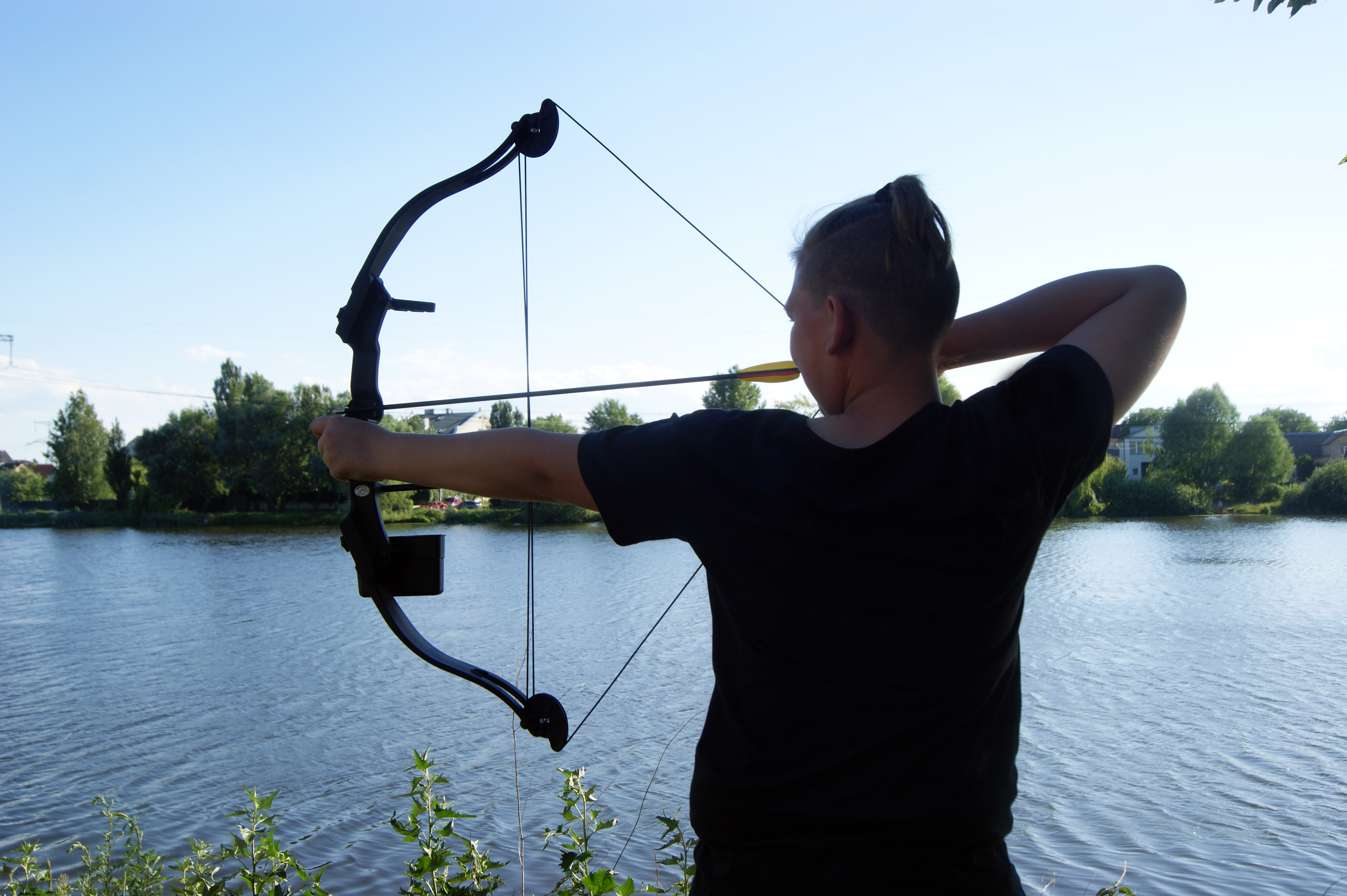 Bow and arrows, hunting by the river, young blue-eyed hunter.